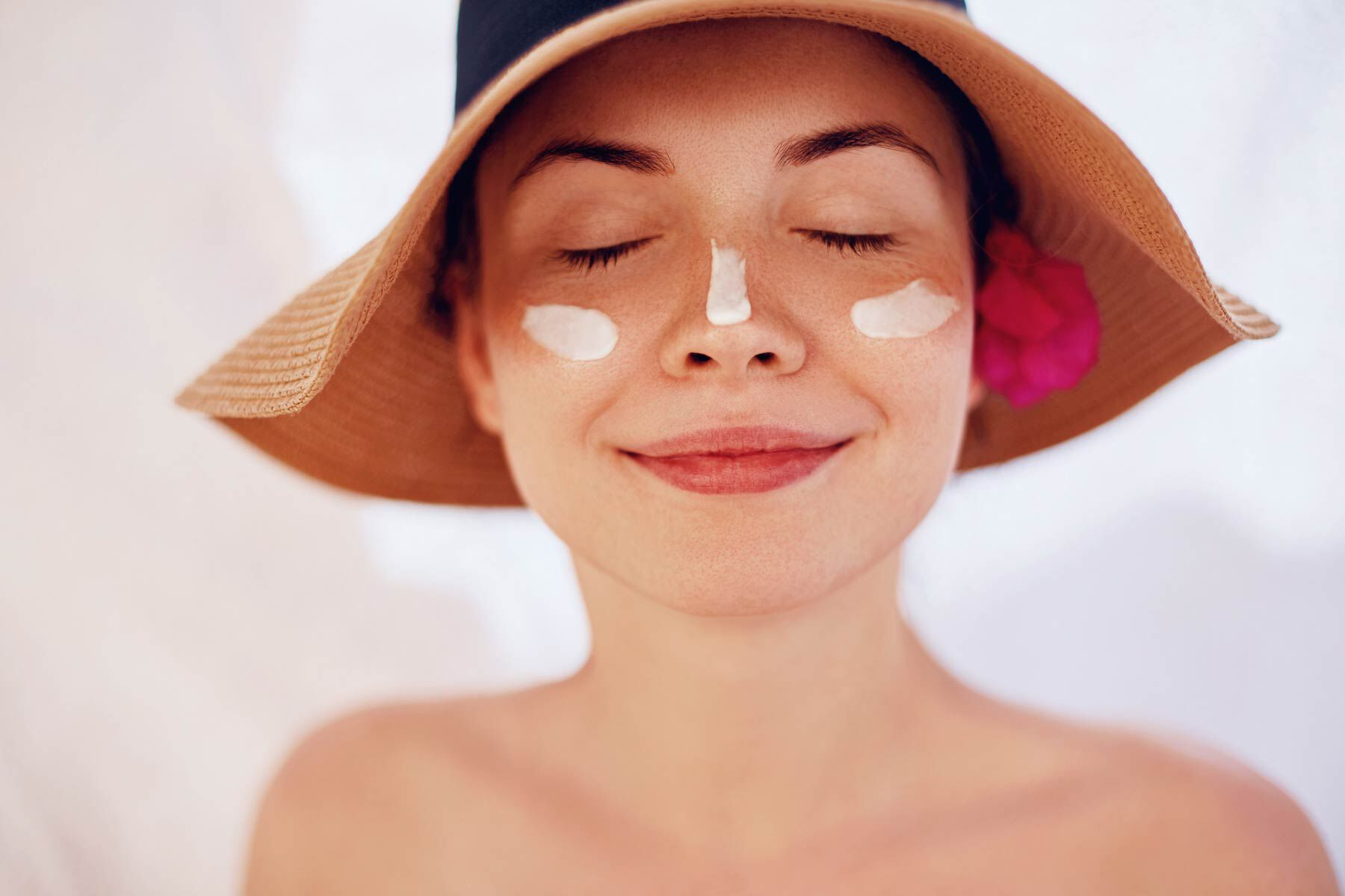 Woman wearing sunscreen and sun hat with eyes closed